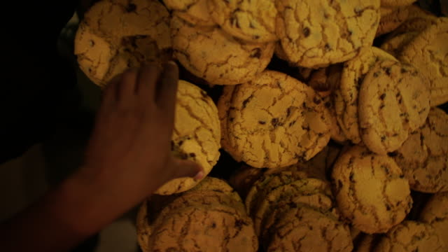 ha slo mo shot of african ethnicity hand picking up cookies in bakery/ johannesburg/ south africa - pane video stock e b–roll