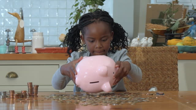 ms shot of african girl playing with coins and piggy bank / cape town, western cape, south africa - savings stock videos and b-roll footage