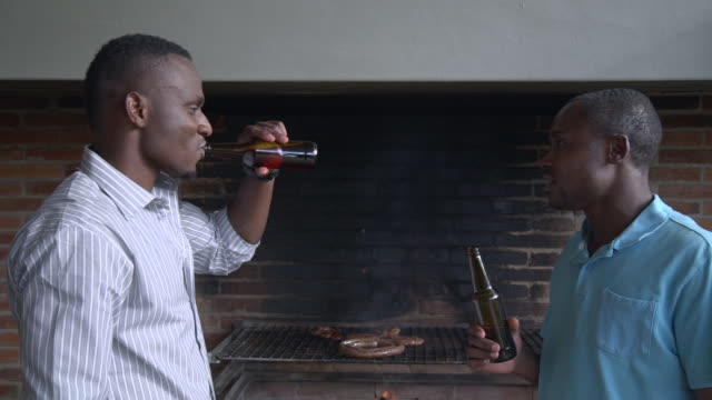 MS Shot of African male friends barbequing and drinking beer / Cape Town, Western Cape, South Africa