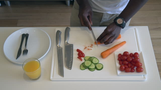 vídeos de stock, filmes e b-roll de ms shot of african man chopping and preparing vegetables / cape town, western cape, south africa - faca faqueiro