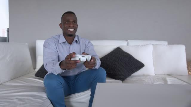 ms pan shot of  african man playing gaming console / cape town, western cape, south africa - computer game control bildbanksvideor och videomaterial från bakom kulisserna