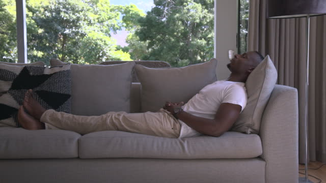 ms pan shot of african man relaxing on sofa / cape town, western cape, south africa - riposarsi video stock e b–roll