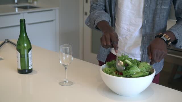vídeos y material grabado en eventos de stock de cu pan shot of african man tossing salad in kitchen / cape town, western cape, south africa - table top shot
