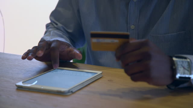 cu shot of african man using digital tablet and credit card/ cape town, western cape, south africa - オンラインショッピング点の映像素材/bロール