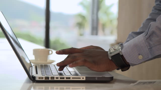 CU PAN Shot of African man using laptop and credit card to shop online / Cape Town, Western Cape, South Africa