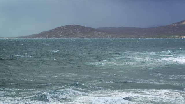 ws pan shot of agitated waves breaking on shore rocks, / harris island, scotland, united kingdom - 2k resolution stock videos and b-roll footage