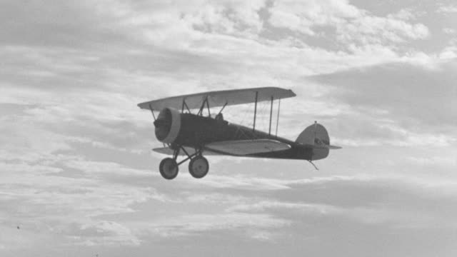 ms ts shot of air to air shot of biplane in flight against cloudy sky - 複葉機点の映像素材/bロール