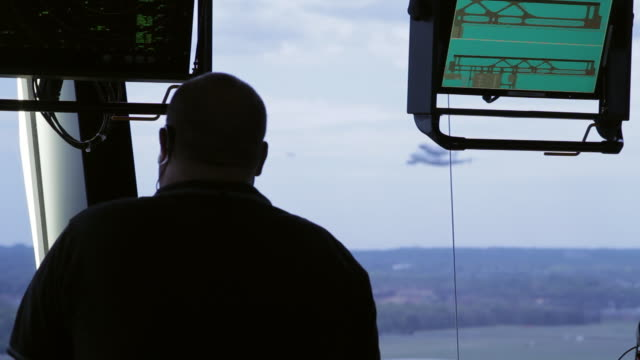 vídeos de stock, filmes e b-roll de ms r/f shot of air traffic controller looking out window of air traffic control tower at dulles airport as nasa shuttle carrier aircraft / sterling, virginia, united states - torre de controle de tráfego aéreo