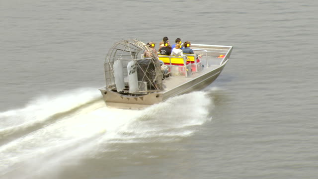 vídeos de stock e filmes b-roll de ws aerial shot of airboat on water with passengers / louisiana, united states - protetor de ouvido
