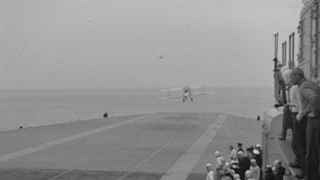 ws shot of aircraft carrier camera to planes take off and ocean in distance - 以前の点の映像素材/bロール
