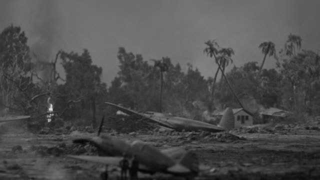 ms pan shot of airfield wreckage with small fires scattered across grounds and downed planes with low flying plane lands - air vehicle stock videos & royalty-free footage