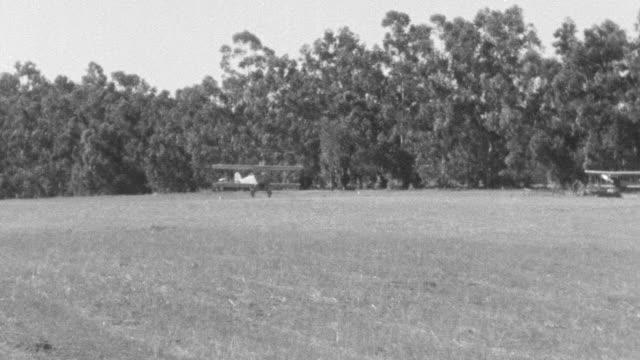 ms ts pan shot of airplanes in flight landing in field - biplane stock videos & royalty-free footage