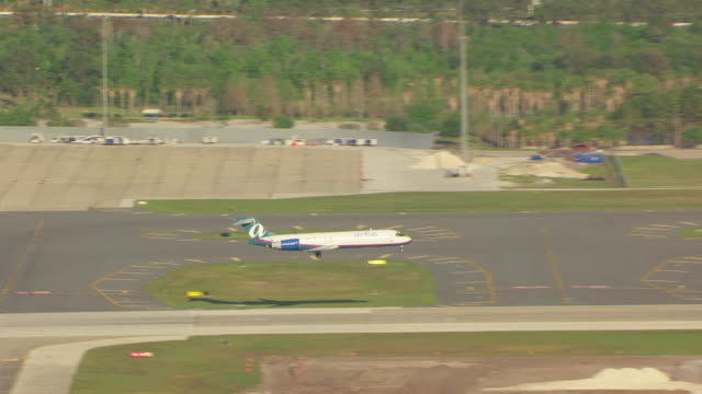 ms aerial zo shot of airtran flying and landing on runway at orlando international airport / orlando, florida, united states - フロリダ州点の映像素材/bロール