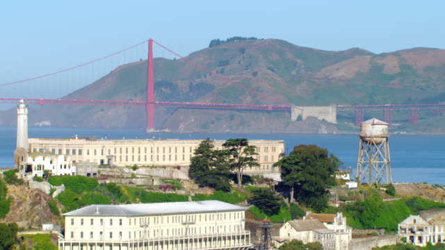 ms zo aerial shot of alcatraz island and prison complex with golden gate bridge / san francisco, california, united states - alcatraz island stock videos & royalty-free footage