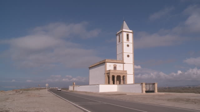 stockvideo's en b-roll-footage met ms shot of almadraba church with car moving on street near cabo de gata beach / monteleva, andalusia, spain - christendom