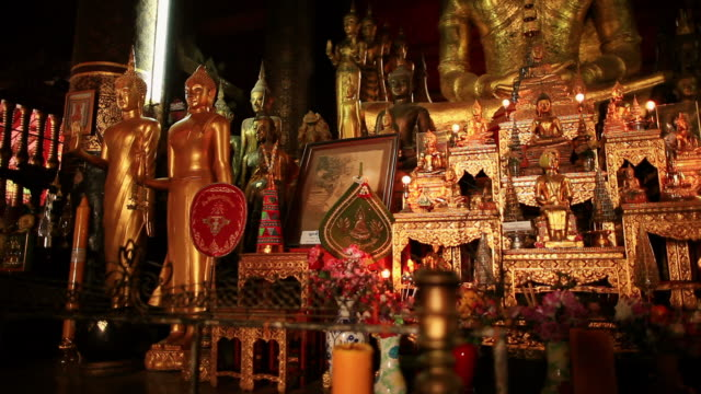 ms pan shot of altar with golden statues pictures and flowers / luang prabang, laos - laos stock videos and b-roll footage
