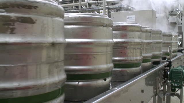 MS Shot of Aluminum beer barrels moving on conveyor at beer production at brewery, Bitburger Pils