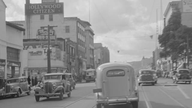 vídeos de stock e filmes b-roll de ms pov shot of ambulance driving down nondescript street looking straight forward and other period cars on road - 1939