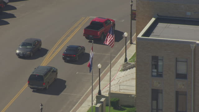 MS AERIAL Shot of American and Missouri state flags in front of Dunklin County Courthouse / Kennett, Missouri, United States
