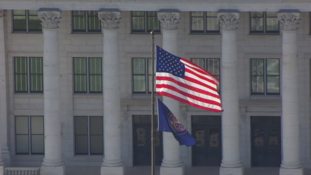 cu aerial zo shot of american flag blowing in wind and capitol building / salt lake city, utah, united states - politics stock videos and b-roll footage