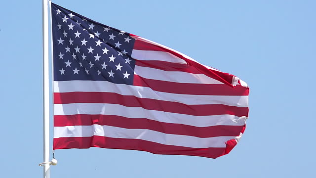 ms slo mo shot of american flag waving in wind / caen, normandy, france - 旗点の映像素材/bロール