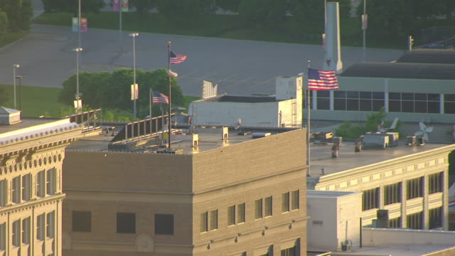 MS AERIAL TS ZO Shot of American flags on top of office building to Omaha World Herald building and office buildings / Omaha, Nebraska, United States