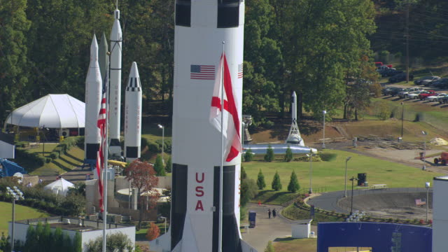 ms aerial shot of american flags with saturn v rocket outside on display and davidson center for space exploration / huntsville, alabama, united states - lenkflugkörper stock-videos und b-roll-filmmaterial