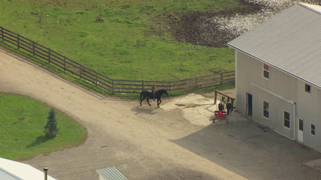 ws zi aerial shot of amish boy riding and parking his horse at stable at farm / bergholz, ohio, united states - pferdestall stock-videos und b-roll-filmmaterial