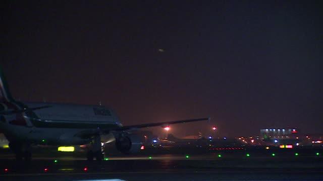 Shot of an Air Italia and Royal Air Maroc aircraft passing through the frame at Heathrow Airport London