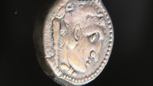 vídeos de stock, filmes e b-roll de shot of an ancient coin depicting the face of hercules - moeda