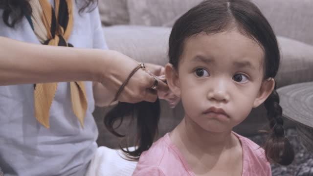 vidéos et rushes de slo mo shot d'une tante tressant les cheveux de sa nièce - tante