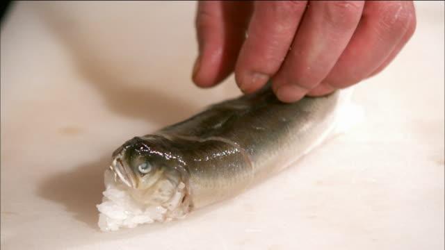 vídeos y material grabado en eventos de stock de shot of an ayu sushi being cut with knife in japan - cortar