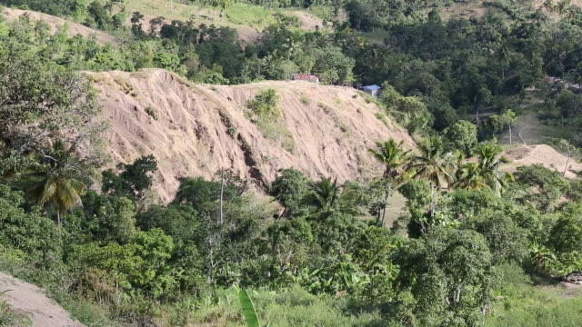 shot of an erosion land surface in a rural area in pilate, haiti with mountains in the background. a small shack with a blue roof on a hill can be... - アフリカ系カリブ人点の映像素材/bロール