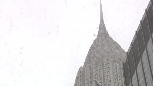 vídeos de stock e filmes b-roll de a shot of an nyc landmarkchrysler buildingduring a snow storm - prédio chrysler