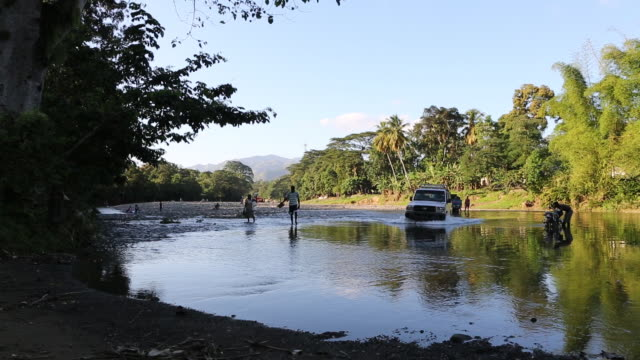 pan shot of an offroad vehicle that is passing a river in a rural area in pilate haiti several people are visible as they are crossing the river too - afro caribbean ethnicity stock videos and b-roll footage