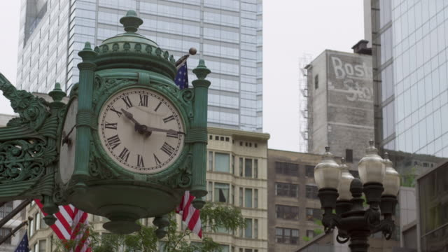 Shot of an old looking clock in Chicago advancing a minute with the city in the background