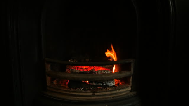 shot of an open fireplace with two glowing wooden logs - fireplace stock videos and b-roll footage