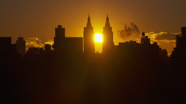 Shot of an orange sun rising between the San Remo Apartments in the Midtown Manhattan Skyline.