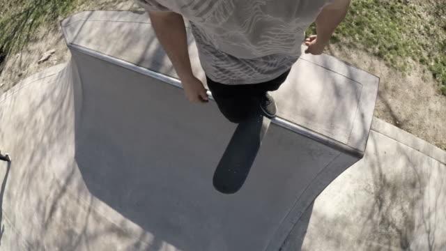 POV shot of an unrecognizable caucasian man skateboarding through a skatepark