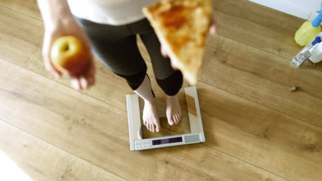 slo mo shot of an unrecognizable woman stepping on the scale with a slice of pizza in one hand and an apple in other. - scales stock videos & royalty-free footage