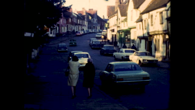 shot of an uphill street in england lots of cars parked by the sidewalk sign on one of the houses has the image of a swan - uphill stock videos & royalty-free footage