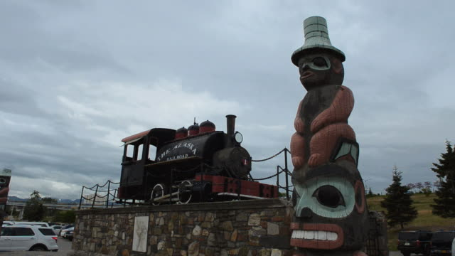 MS Shot of Anchorage Alaska famous Alaska Railroad old rail car and totem pole in city railroad / Anchorage, Alaska, United States