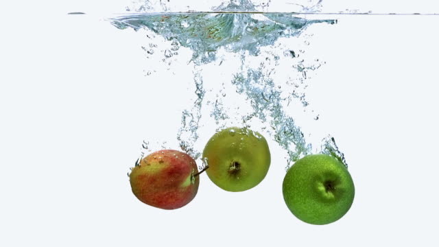 cu slo mo shot of apples, malus domestica, fruits entering water against white background / calvados, normandy, france - calvados stock-videos und b-roll-filmmaterial