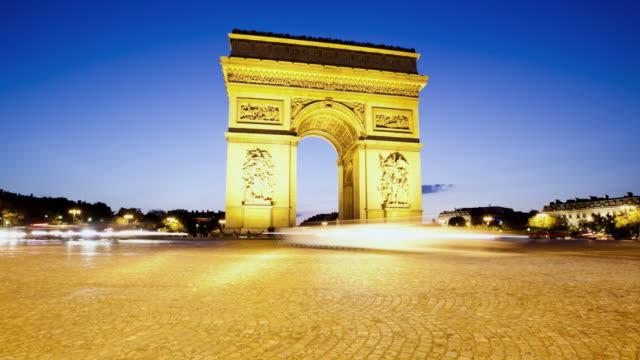 vidéos et rushes de ms t/l tu shot of arc de triomphe at dusk with traffic / paris, ile-de-france, france - arc élément architectural
