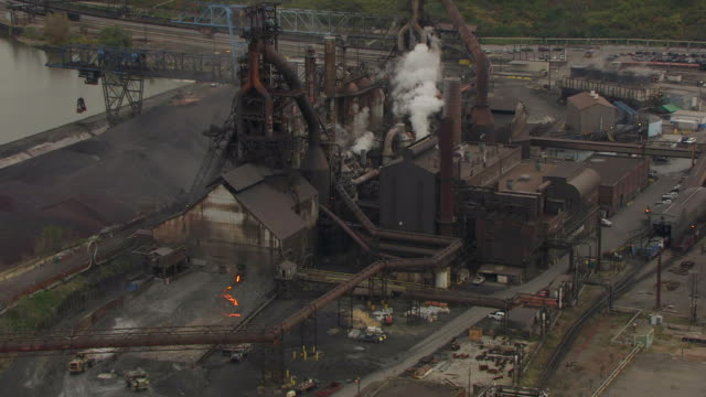 ws td zi aerial shot of arcelor mittal steel factory and tractor driving by pouring molten steel / cleveland, ohio, united states - cleveland ohio stock videos & royalty-free footage