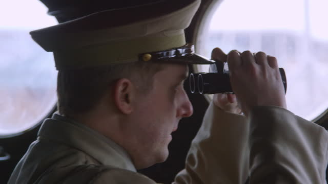 cu shot of army officer looks through binoculars from the command cabin of lst / evansville, indiana, united states - militärschiff stock-videos und b-roll-filmmaterial