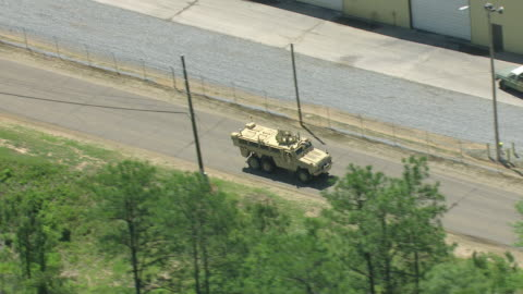 ms aerial ts shot of army vehicle driving on road and turns onto another street at military post camp shelby in broad day light / mississippi, united states - armoured vehicle stock videos & royalty-free footage