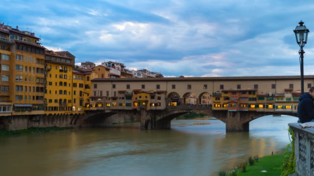 ms t/l pan shot of arno river, ponte vecchio at dusk / florence, tuscany, italy - ponte stock videos & royalty-free footage