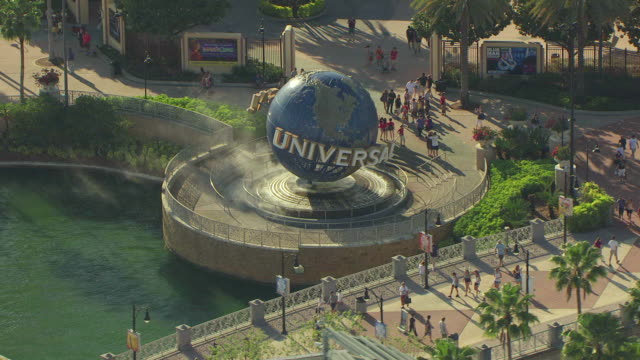 ms aerial shot of around moving globe with universal signage on it and people walking and taking pictures around globe / orlando, florida, united states - orlando florida stock videos & royalty-free footage