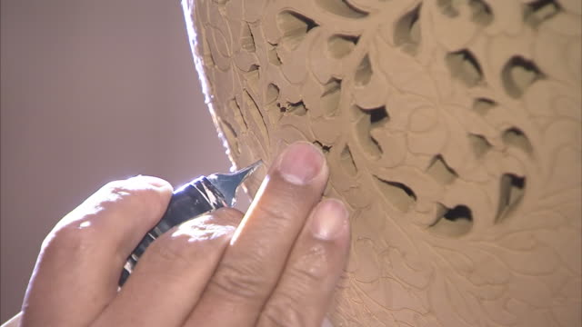 Shot of Artisan Engraving and Carving a pottery using by chisel at Cheongju International Craft Biennale